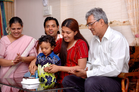 South Asian Indian small boy of 3 years cutting birthday cake