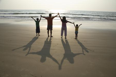 South Asian Indian parent and children holding hands facing sun with long shadows behind them on sand at seashore,Shiroda,Dist. Sindhudurga,Maharashtra,India,and