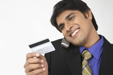 conferring: Executive holding mobile phone and looking at credit debit card