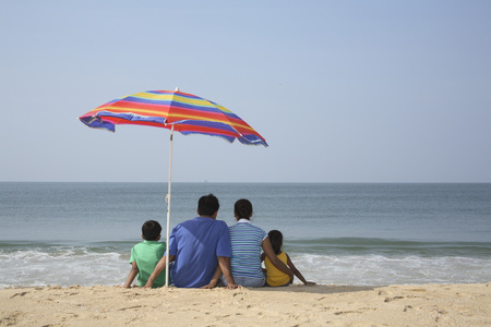 South Asian Indian parent and children sitting under shadow of colourful umbrella facing sea on seashore,Shiroda,Dist. Sindhudurga,Maharashtra,India