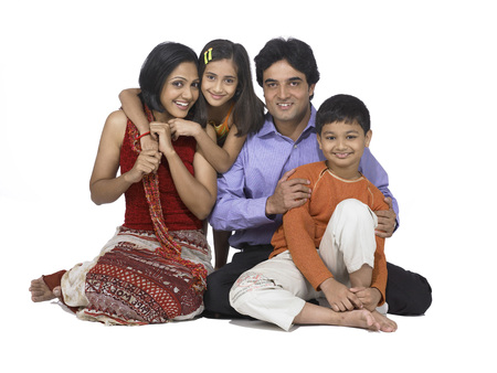 South Asian Indian family with father mother son and daughter sitting smiling and looking at camera