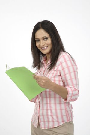Young girl with hair open holding open book in her hand and smiling