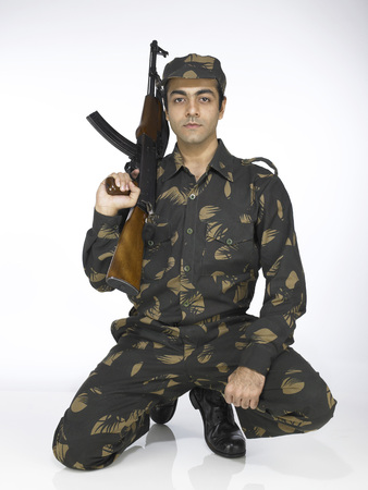 Indian army soldier sitting on knee holding AK-47 gun Stock Photo