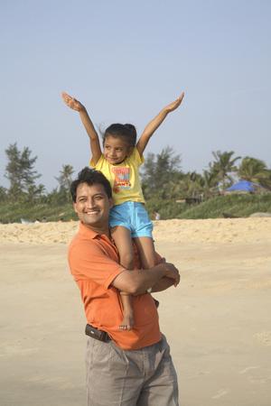 South Asian Indian daughter spread hands upward sitting on father shoulder on seashore,Shiroda,Dist. Sindhudurga,Maharashtra,India Stok Fotoğraf - 85732430