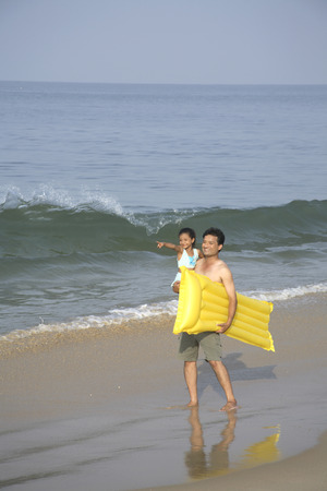 South Asian Indian father holding daughter and carrying yellow floating air bed in arm on seashore,Shiroda,Dist. Sindhudurga,Maharashtra,India Stock Photo