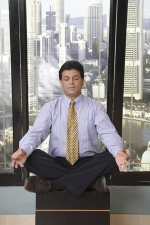 Executive sitting on small table doing yoga meditation in office at top floors of skyscraper in modern city