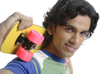 Teenage boy standing with skate board holding on shoulder