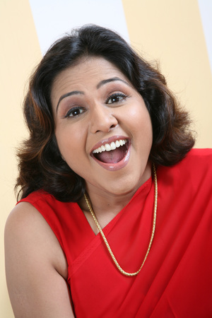 South Asian Indian young lady wearing red sari and gold chain laughing