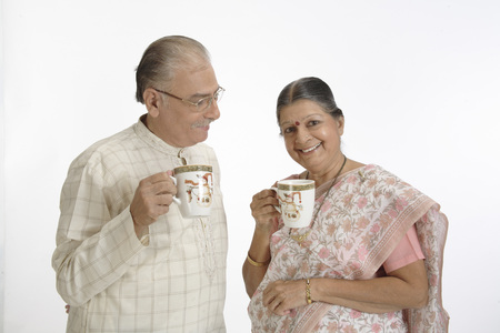 Old happy couple holding tea or coffee mugs in hand and smiling