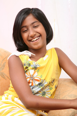 South Asian Indian young girl seating on sofa and smiling