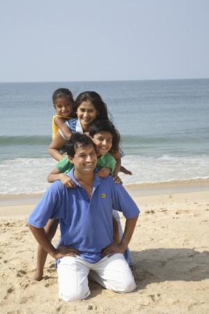 South Asian Indian parent and children standing behind each other on seashore,Shiroda,Dist. Sindhudurga,Maharashtra,India Stock Photo