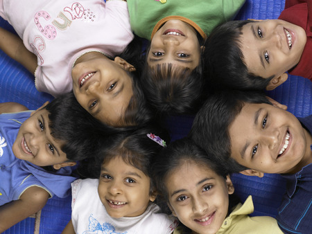 South Asian Indian boys and girls lay down on floor in nursery school Stock Photo