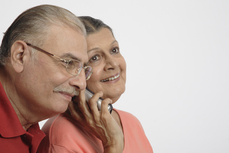 Old couple,Old lady holding cordless phone to right ear and old man coming close to listen to it
