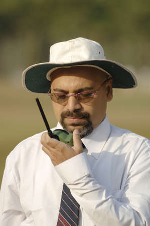 South Asian Indian cricket umpire talking to third umpire on walkie-talkie standing behind wicket on pitch