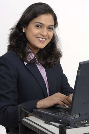 operating key: Office going South Asian Indian lady operating laptop