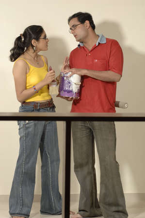 contemporary living room: Backview of South Asian Indian man and woman holding can and paint brush  discussing about paint in new flat