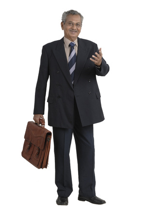 Office going South Asian Indian active old man holding leather bag explaining something  Stock Photo