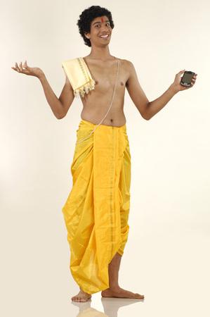 b5fd49ddbb South Asian Indian teenager boy wearing traditional yellow silk dhoti  Pitambar holy thread holding pocket p.c.