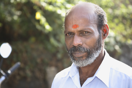 South Indian man with tika on forehead with sandal or saffron paste with black grey moustaches and beard