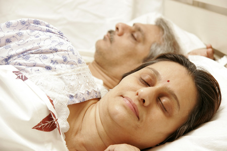 South Asian Indian middle-aged couple having sound asleep on bed 686F,646 Stock Photo