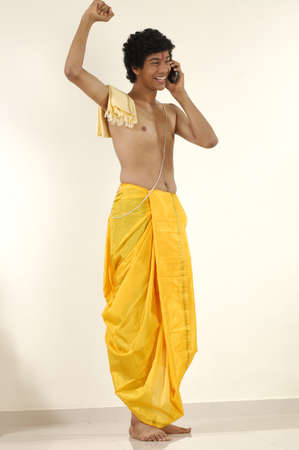 dhoti: South Asian Indian teenager boy wearing traditional yellow silk dhoti Pitambar holy thread talking on pocket p.c. phone,Bombay Mumbai,Maharashtra,India
