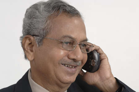 Office going South Asian Indian active old man talking on pocket pc phone