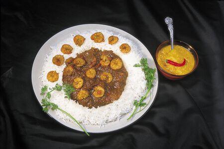 채식주의 식사가 아닌 새우 Patti 카레와 밥은 검은 색 바탕에 접시에 담겨 있습니다.