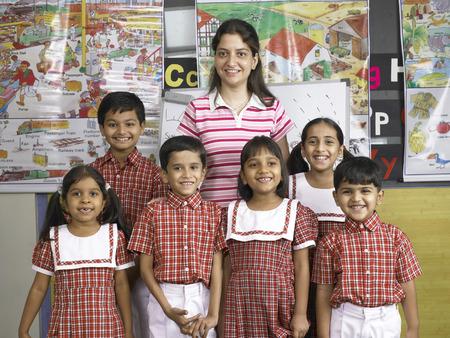 南アジアのインド人教師が保育園で子供たちと一緒に立っている