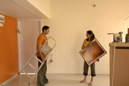 South Asian Indian man and woman holding photo frame and table in new flat