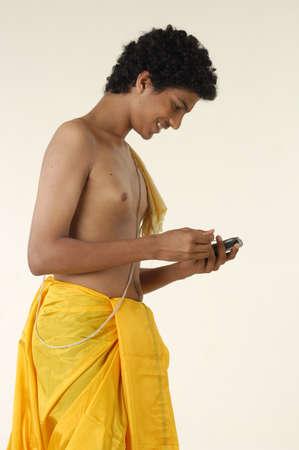 dhoti: South Asian Indian teenager boy wearing traditional yellow silk dhoti Pitambar holy thread using pocket p.c. phone with blue tooth,Bombay Mumbai,Maharashtra,India