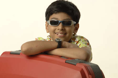 South Asian Indian boy of ten years old going on holiday wearing goggles hands on suitcase
