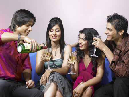 nightspot: South Asian Indian man pouring champagne in glass of friend celebrating party LANG_EVOIMAGES