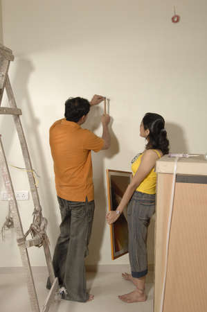 contemporary living room: South Asian Indian man hammering nail on wall and woman holding photo frame in new flat