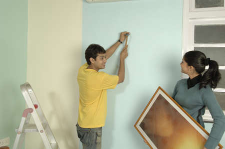 drawing room: South Asian Indian young couple planning interior of their new flat