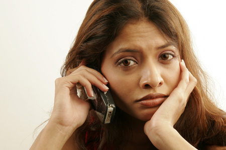 South Asian Indian teenager girl wearing red colour contact lenses in eyes disappointingly talking on mobile phone