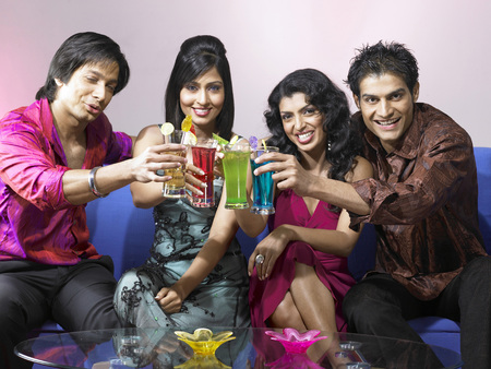 nightspot: South Asian Indian men and women toasting drink glasses celebrating party