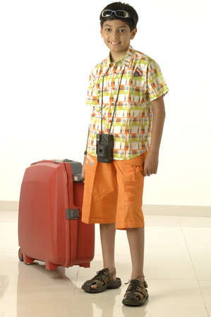 South Asian Indian boy of ten years old going on holiday taking camera and suitcase