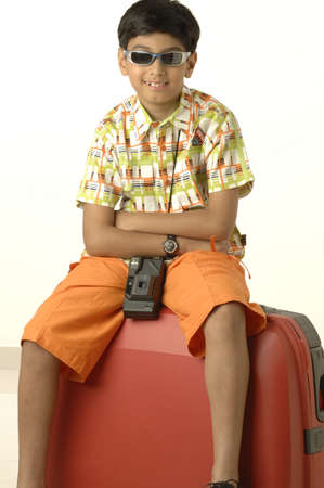 South Asian Indian boy of ten years old going on holiday wearing goggles taking  camera and sitting on suitcase Stock Photo