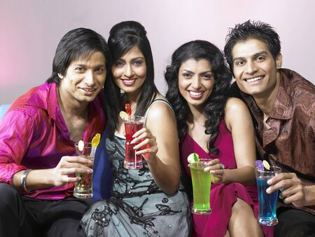 nightspot: South Asian Indian men and women holding drink glasses celebrating party