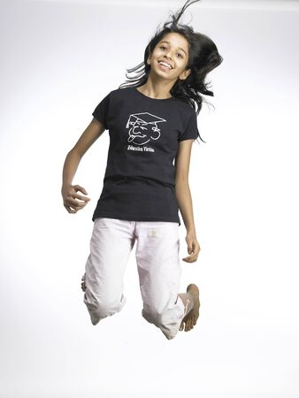 South Asian Indian young girl jumping with joy Imagens