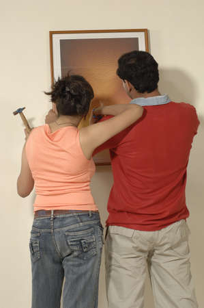 Backview of South Asian Indian man and woman adjusting photo frame on wall in new flat Stock Photo