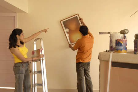 drawing room: South Asian Indian woman showing position of photo frame to man adjusting on wall in new flat