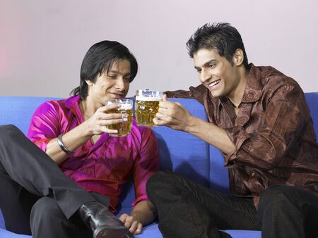 nightspot: South Asian Indian men toasting drink glasses celebrating party LANG_EVOIMAGES