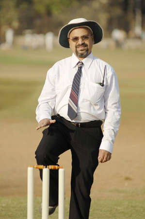 South Asian Indian cricket umpire indicating leg bye sign by hand touching raised knee standing behind wicket on pitch Stock Photo