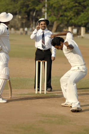 Indian umpire indicating out sign by raising index finger above head and bowler enjoying in cricket match Stock Photo