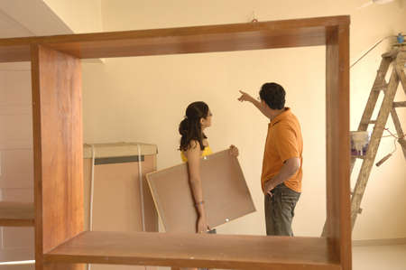 drawing room: South Asian Indian man showing position of photo frame to woman in new flat
