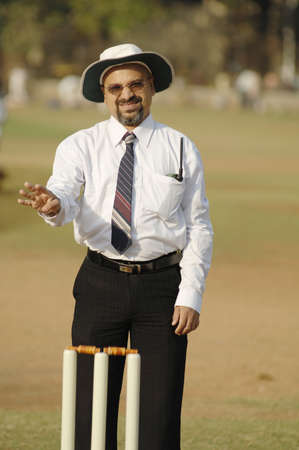 South Asian Indian cricket umpire indicating four runs or boundary sign waving arm standing behind wicket on pitch
