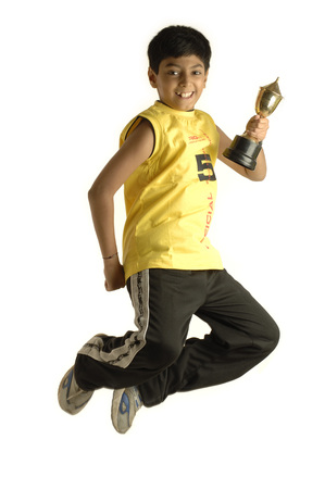 South Asian Indian boy of ten years old winner of award holding trophy and  jumping in air with joy