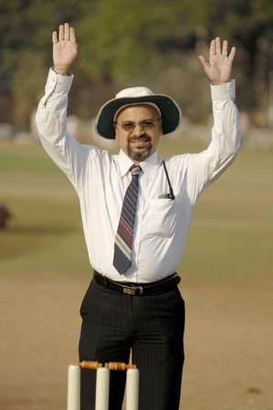 South Asian Indian cricket umpire indicating six runs sign by raising both hands above head standing behind wicket on pitch Stock Photo