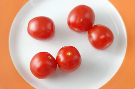 Vegetable,Fruit,Red baby tomatoes on white plate on orange background Stock Photo